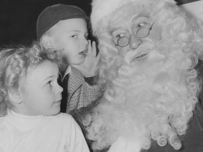 Mark Walters, 4, tells Santa what he wanted for Christmas while Melanie Dennison, 5, looks on.  Santa made a guest appearance at the 1957 Indianapolis Star Gift and Hobby Show.