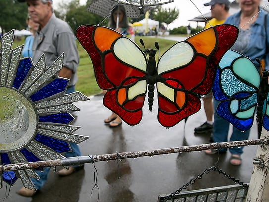 Rain drops on stain glass and wet greenway as visitors