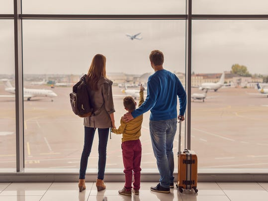 Family looking out window at airport