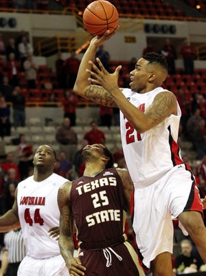 UL's Shawn Long (21) puts up a shot as Texas State's Joel Wright (25) defends in an NCAA basketball game Monday at the Cajundome in Lafayette.By Leslie WestbrookJanuary 13, 2014