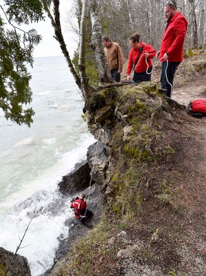 Firefighter Zack Defere looks between rocks for two men whose kayaks capsized Friday off Cave Point County Park.