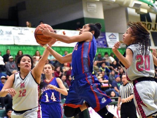 Las Cruces High's Brooke Salmon splits Trojan defenders Raena Texillo (left) and Genesis Tellez (right) as she goes in for a lay up on Tuesday night.