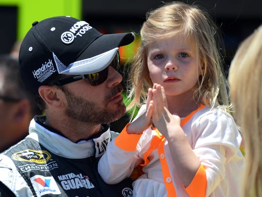 Driver Jimmie Johnson holds his daughter Genevieve, right, before driving in the NASCAR Sprint Cup series auto race at Dover International Speedway, Sunday, June 1, 2014, in Dover, Del.