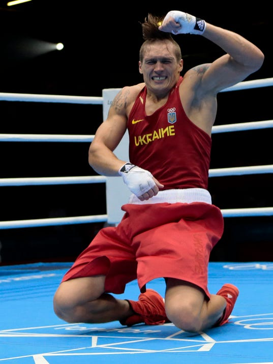 FILe - In this Aug. 11, 2012 file photo, Oleksandr Usyk of Ukraine, dances after winning against Clemente Russo of Italy, in their heavyweight 91-kg gold medal boxing match at the 2012 Summer Olympics in London. Usyk was so excited about winning the heavyweight gold medal that he broke into a traditional Ukrainian dance in the ring. But the Ukraine he pointed to so proudly on the front of his boxing uniform is a different country from the one two years ago. (AP Photo/Ivan Sekretarev, File)