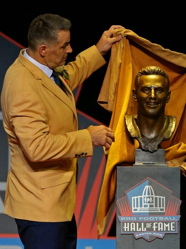 Aug 5, 2017; Canton, OH, USA; Kurt Warner pulls back the cloth on his bust with wife Brenda Warner (right) during the 2017 NFL Hall of Fame enshrinement at Tom Benson Hall of Fame Stadium.