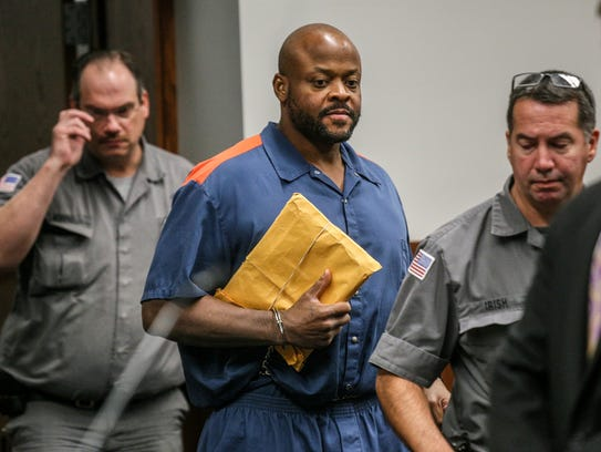 Defendant Kevin Beverly is escorted by guards to his