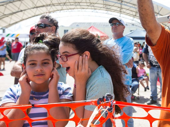 Two young girls hold their ears as the Blue Angels take off at the start of their performance during the Wings Over South Texas air show at the Naval Air Station Kingsville, Saturday, April 9, 2016.