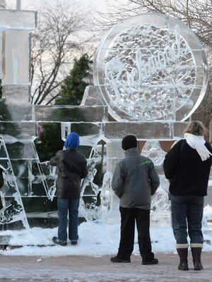 A family takes a closer look at an ice sculpture on East Main and 10th streets during the 2015 Meltdown Winter Ice Festival.