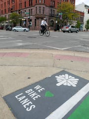 A cyclist rides past a decoration promoting bike lanes on Tuesday, Sept. 22, 2015, in Cedar Rapids, Iowa.