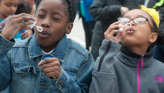 Charles Myles, left, and Kayla Jackson blow bubbles  for 60 seconds to celebrate autism awareness at Winslow Elementary School in Vineland.