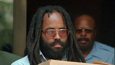 Convicted police killer and death-row activist Mumia Abu-Jamal leaves Philadelphia's City Hall after a hearing. Mumia Abu-Jamal, a one-time death row inmate now serving a life sentence for the 1981 murder of a Philadelphia police officer spoke to students graduating from a Vermont college on Sunday encouraging them to strive to transform the world.