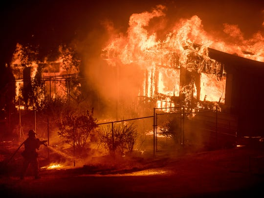 In this Sunday, July 9, 2017, file photo, a firefighter