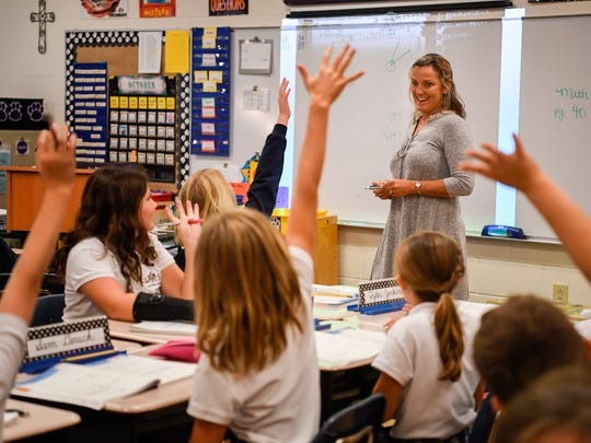Teacher Sherrie Hill helps students in the fourth grade