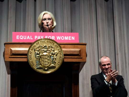 Governor Phil Murphy, right, applauds as Lilly Ledbetter