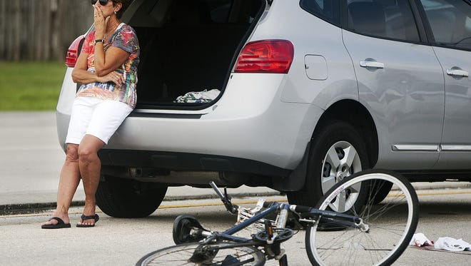 In this September photo, a driver involved in a crash between two vehicles and a bicyclist on Bonita Beach Road reacts to the situation.