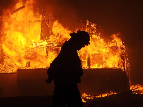 A firefighter walks past a burning home at the corner of North Fir and Buena Vista Street at 2 a.m. Dec. 5.