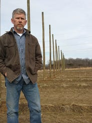 Dave Volkman stands alongside his hops field at Ohio