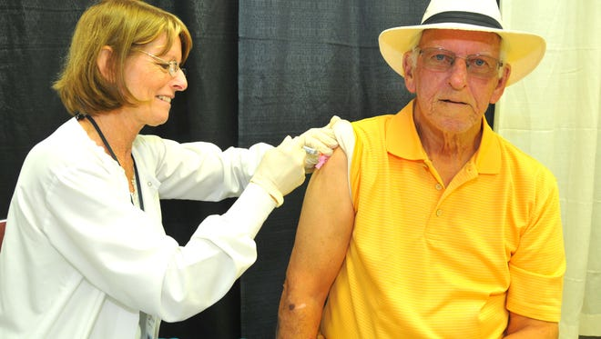 Nancy Cook with the Visiting Nurses Association gives William Tinsley of Titusville a high dose flu shot at Senior Fest. Hundreds of seniors have packed the Melbourne Auditorium as part of the the 16th annual Senior Fest on Friday. The event featured a host of vendors representing both businesses and public agencies including the Titusville, Satellite Beach, West Melbourne, Melbourne Police Departments and the Brevard County Sheriff's Office.