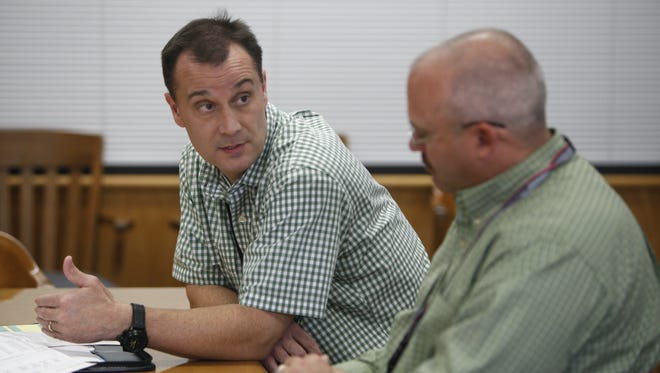 Greene County Administrator Chris Coulter talks with Sheriff Jim Arnott about how the county will handle dog bites on Tuesday, Oct. 28, 2014.