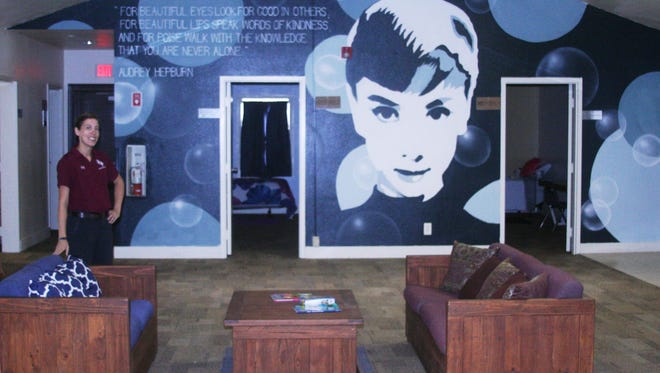 Rebekah Graham, the new program director at Sierra Sage Academy, formerly known as Silver State Academy, stands in the lobby of one of the redesigned dormitories that features a new Audrey Hepburn mural.