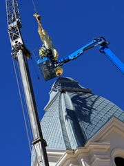 Construction workers place a statue of the Angel Moroni