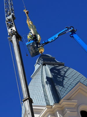 Construction workers place a statue of the Angel Moroni on top of the Cedar City Temple of The Church of Jesus Christ of Latter-day Saints on Thursday.