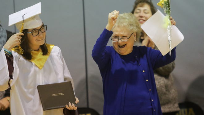 Cindy Mann, head of Padua Academy, cheers her on 19-year-old Kelly Muschiatti, who graduated after surviving a car crash.