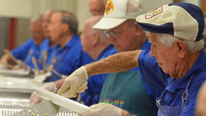 Bill Lewis, right, dishes up the chow with his fellow volunteers in this file photo from a previous San Marco Catholic Church's Knights of Columbus Friday fish fry. Lance Shearer/Eagle Correspondent