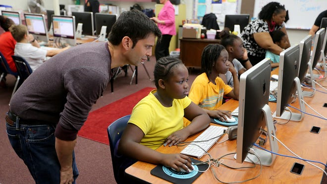 Jason Stamm helps Jakyra Harvin and other students at Springwood Elementary School in a recent computer skills session presented by Massive Academy.
