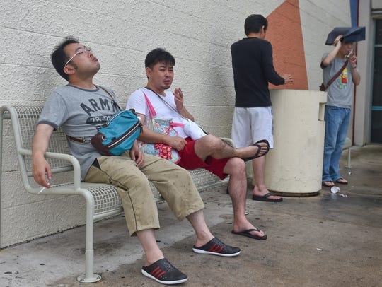 In this file photo, shoppers take a smoke break in a designated smoking area outside Guam Premier Outlets in Tamuning. Guam's legal smoking age will increase to age 21 on Jan. 1, 2018.