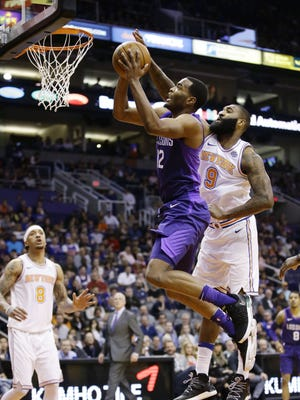 Phoenix Suns T.J. Warren drives to the basket past New York Knicks center Kyle O'Quinn in the 1st half at Taking Stick Resort Arena on Jan. 26, 2018 in Phoenix, Ariz.