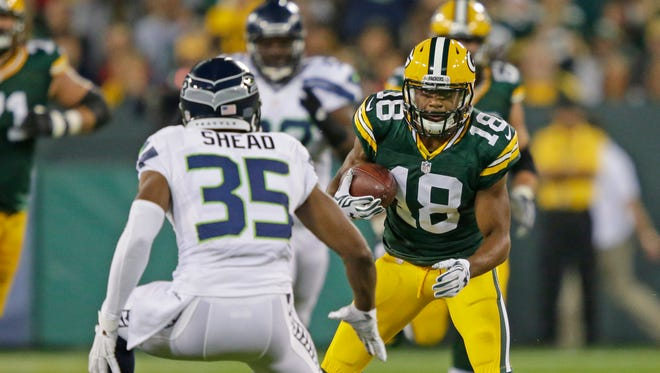 Green Bay Packers wide receiver Randall Cobb (18) tries to elude strong safety DeShawn Shead (35) against the Seattle Seahawks at Lambeau Field.