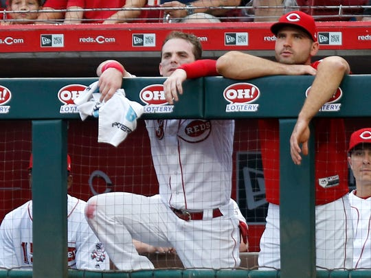 Cincinnati Reds second baseman Scooter Gennett (3) and first baseman Joey Votto (19) watch from the dugout against the San Francisco Giants during the first inning at Great American Ball Park.
