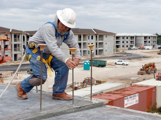 Alex Macmenemy marks off the building layout for masons at Channelside Apartments in Fort Myers Tuesday, November 18.