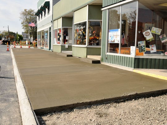 Coffee Express, Sew Much More and Gifts Galore, The End Zone, Lilly & Gert's and Frederick Insurance Agency got new sidewalks in the 100 block of West Second Street on Monday afternoon.