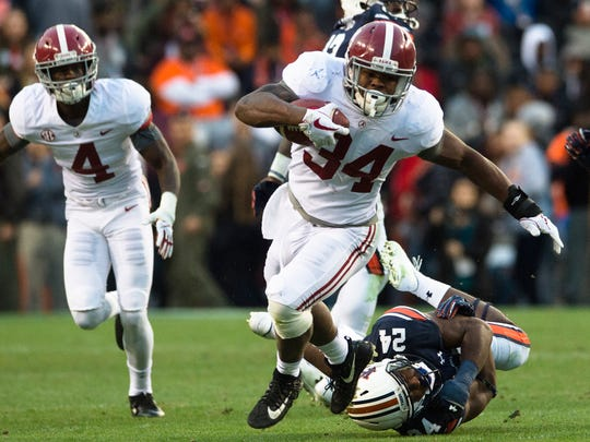 Alabama running back Damien Harris (34) slips a tackle attempt by during the Iron Bowl NCAA football game between Auburn and Alabama on Saturday, Nov. 25, 2017, in Auburn, Ala. Auburn fans roll Toomer's Corner after the Iron Bowl NCAA football game between Auburn and Alabama on Saturday, Nov. 25, 2017, in Auburn, Ala. Auburn defeated Alabama 26-14.