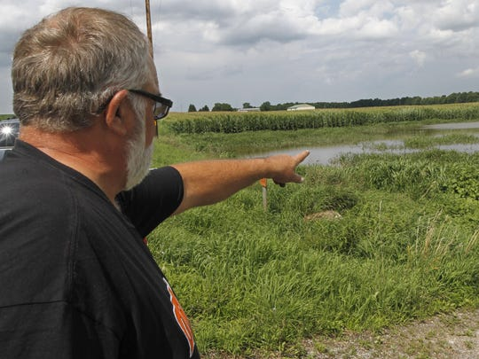Bill Carr points to his flooded fields of corn and soybeans on his Carr Farms land in Le Roy.