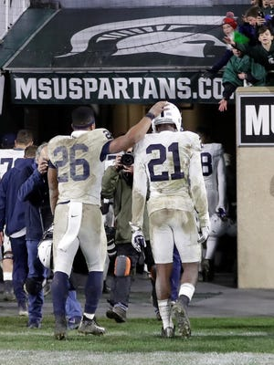 Penn State running back Saquon Barkley (26) and cornerback Amani Oruwariye (21) walk out of Spartan Stadium after an NCAA college football game, Saturday, Nov. 4, 2017, in East Lansing, Mich. Michigan State won 27-24.