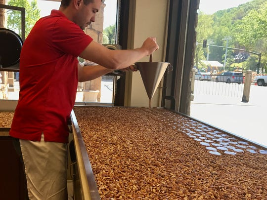 Scott Rowe is adding caramel to pecans as he makes