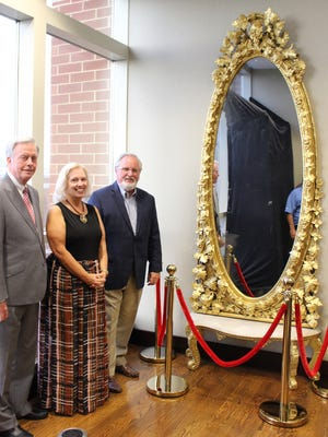 Fred Landiss, Carolyn Stier Ferrell and Sammy Stuard stand with the antique mirror that has been returned to its original location.