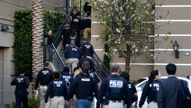 Federal agents enter an upscale apartment complex on March 3, 2015, in Irvine, Calif., to conduct a crackdown on alleged maternity tourism rings.