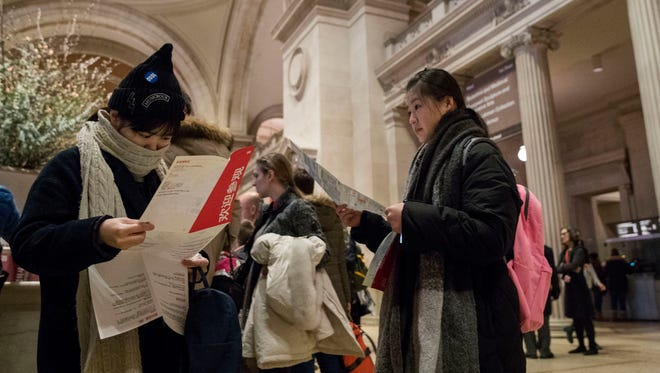 Visitors to the Metropolitan Museum of Art inspect the map of the museum after purchasing a ticket, Thursday, Jan. 4, 2018, in New York. Starting March 1, the museum will charge a mandatory $25 entrance fee to most adult visitors who don't live in New York state, the Met's president and CEO, Daniel Weiss, announced Thursday. Admission will still be pay-what-you-wish for New Yorkers.