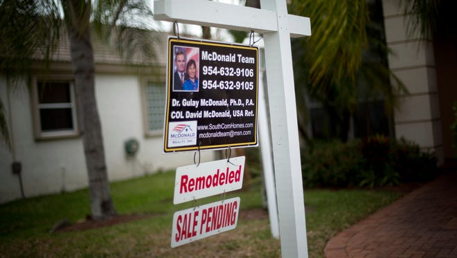 A for sale sign hangs outside a home in Pembroke Pines, Fla.