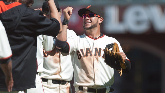 Giants center fielder Gregor Blanco celebrates with teammates after defeating the Pittsburgh Pirates at AT&T Park.