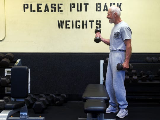 Rolf Soedergren, 75, uses free weights during his workout