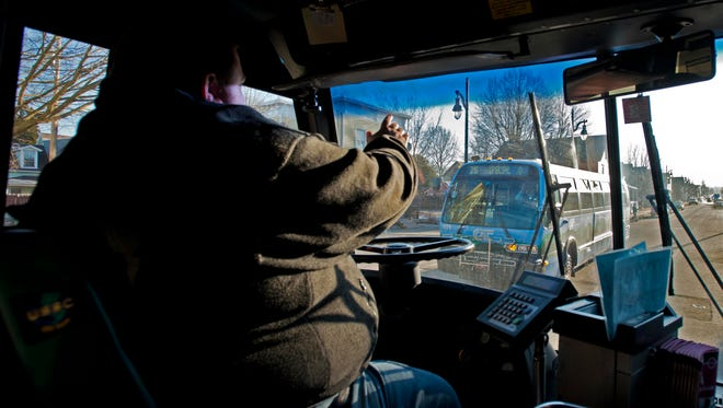 Sean McCutcheon, a field supervisor at CCTA, waves to a passing bus while driving a route on North Street in Burlington on April 4.