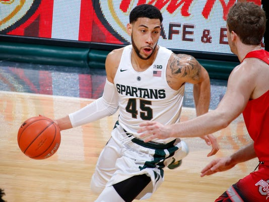 Michigan State's Denzel Valentine (45) drives against Ohio State's Mickey Mitchell during the first half of an NCAA college basketball game, Saturday, March 5, 2016, in East Lansing, Mich. (AP Photo/Al Goldis)