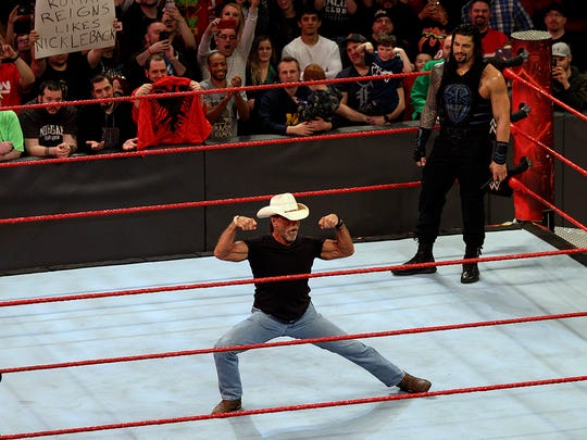 "Shawn Michaels poses for the crowd as Roman Reigns looks on during WWE ""Monday Night Raw"" on March 13, 2017, at Joe Louis Arena in Detroit."