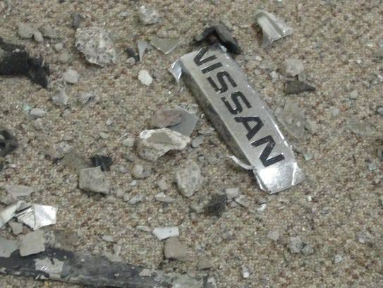 A Nissan nameplate was among the car parts and building