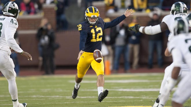 Michigan's Blake O'Neill punts in the fourth quarter Saturday against Michigan State.